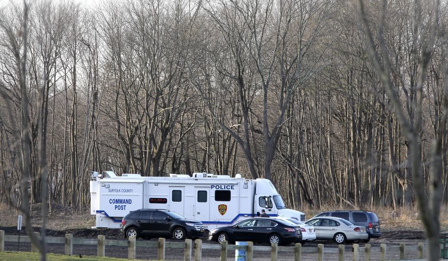 Emergency vehicles are parked near the site where four bodies were discovered in Central Islip, N.Y., Thursday, April 13, 2017. Police say the bodies of four apparent homicide victims have been found in a Long Island park, east of New York City.   (AP Photo/Seth Wenig)