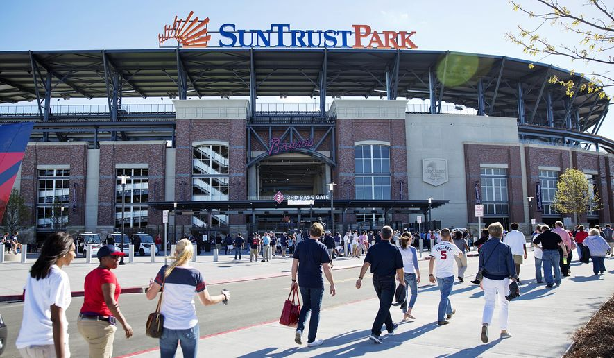 FILE - In this March 31, 2017, file photo, fans head to SunTrust Park before the Atlanta Braves open their new ballpark for an exhibition spring training baseball game against the New York Yankees, in Atlanta. After a short 20-year stay at Turner Field, the Braves begin their SunTrust Park era on Friday night, April 14 in their home opener against the San Diego Padres.  (AP Photo/David Goldman, File)