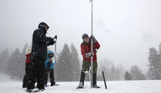 FILE - In this March 30, 2017 file photo, Frank Gehrke, right, chief of the California Cooperative Snow Surveys Program for the Department of Water Resources, lifts the survey tube out of the snowpack depth during the manual snow survey at Phillips Station near Echo Summit, Calif. The National Weather Service says this is now the wettest winter on record in the Northern California mountains. Weather Service officials say an index of precipitation at eight stations in the northern Sierra Nevada surpassed the old record at about 4 a.m. Thursday, April 13, 2017, with just under 90 inches of rain and snow.   (AP Photo/Rich Pedroncelli, File)
