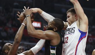 FILE - In this March 15, 2017, file photo, Milwaukee Bucks center Greg Monroe, center, vies for a rebound with Los Angeles Clippers guard Chris Paul, left, and forward Blake Griffin during the first half of an NBA basketball game, in Los Angeles. The Clippers are heading into the playoffs on a seven-game winning streak, eager to atone for their postseason missteps the last three years. They'll open against the Utah Jazz, with Blake Griffin and Chris Paul still trying to get past the second round in their sixth season together.  (AP Photo/Chris Carlson, File)