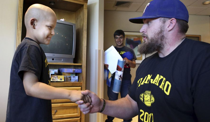 In this photo made Saturday, April 7, 2017, Cancer patient Jayro Ponce, 9, left, meets New York Giants center Weston Richburg at the Harrington Cancer Center in Amarillo, Texas. (Lauren Koski/Amarillo Globe-News via AP)