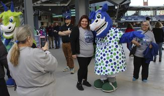 Elizabeth Ortiz, 27, of East Hartford, Conn., poses with Hartford Yard Goats mascot Chew Chew at opening day of Hartford's new minor league baseball stadium in Hartford, Conn., Thursday, April 13, 2017. The city and its minor league baseball team are celebrating opening day at the new 6,000-seat stadium, albeit a year late and millions of dollars over budget. (AP Photo/Pat Eaton-Robb)