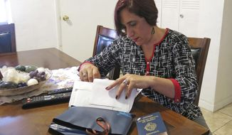 In this April 4, 2017 photo, Rosana Araujo goes through her personal documents at her home in Miami, after a recent trip. Araujo, who is in the country illegally, has an Uruguayan passport and a form that shows the date she arrived in Miami under a visa waiver program fourteen years ago. Since 2007, some 600,000 more people overstayed their visas than entered the country illegally, the New York City-based Center for Migration Studies found. (AP Photo/Adriana Gomez Licon)