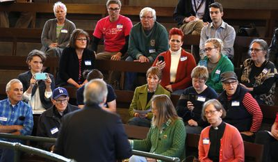 Rep. David Young, R-Iowa, left, speaks during a town hall meeting, Wednesday, April 12, 2017, in Des Moines, Iowa. Rebuffing President Donald Trump and Republican leaders on the GOP health care bill seemed like a major political misstep for Young, who quickly was punished by a political action committee linked to Speaker Paul Ryan. Nearly three weeks later, voters in Young's southwestern Iowa district, Republicans and Democrats, say the GOP congressman made the right move. (AP Photo/Charlie Neibergall)