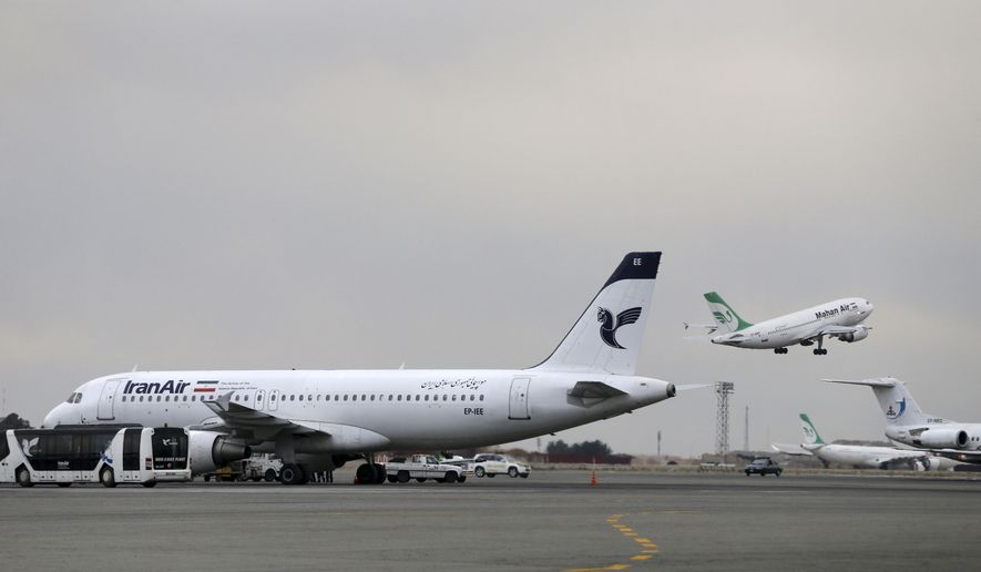 FILE - In this Feb. 7, 2016, file photo, an Iranian Mahan Air passenger plane takes off as a plane of Iran's national air carrier Iran Air, left, is parked at Mehrabad airport in Tehran, Iran. European airplane manufacturer ATR said it signed a deal with Iran Air for 20 aircraft with option for 20 more on Thursday, April 13, 2017. (AP Photo/Vahid Salemi, File)