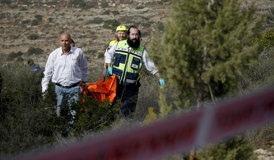 FILE - In this Dec. 19, 2010 file photo, Israeli rescue workers carry the body of U.S. tourist Kristine Luken after she was found in a wooded area near the village of Mata, outside Jerusalem. Two Palestinian men convicted in Israel of murdering Luken who was hiking near an Israeli archaeological site could face charges in the U.S. if they're ever released from an Israeli prison.  (AP Photo/Tara Todras-Whitehill, File)