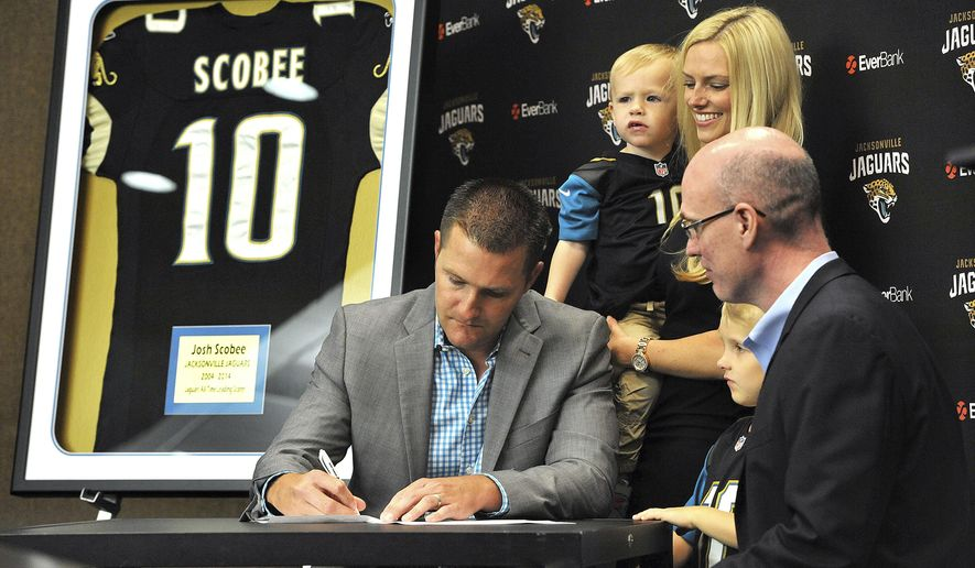 Veteran place-kicker Josh Scobee, left, signs a ceremonial one-day contract with the Jacksonville Jaguars NFL football team as his wife, Melissa, and children, Jacob, 5, David, 2, and Jaguars director of football operations Tim Walsh look on before officially retiring Thursday, April 13, 2017, in Jacksonville, Fla. (Bruce Lipsky/The Florida Times-Union via AP)