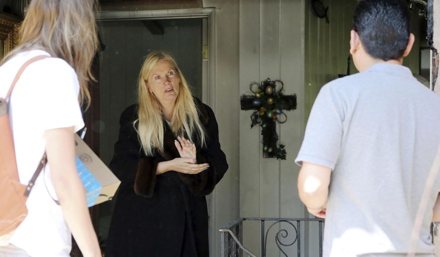 "Gunilla Persson, star of the Swedish television reality show ""Svenska Hollywoodfruar,"" or ""Swedish Hollywood Wives"" speaks to visitors after a predawn fire severely damaged her home and a neighbor's in the Pacific Palisades area of Los Angeles Thursday, April 13, 2017. (AP Photo/Reed Saxon)"