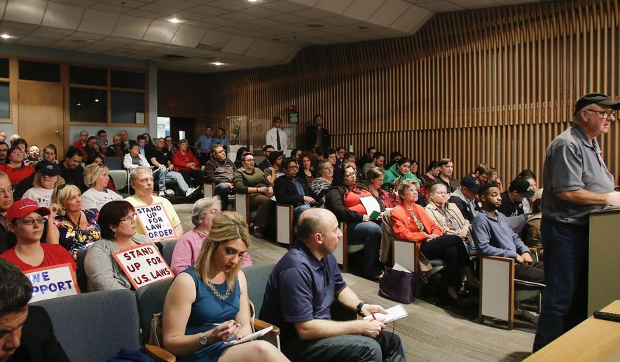 """People crowd the Lansing City Council chambers for a special meeting in Lansing, Mich., Wednesday, April 12, 2017. Michigan's capital city on Wednesday rescinded its decision to deem itself a """"sanctuary city"""" protecting immigrants, bowing to concerns from the business community that the ambiguous, contentious term may draw unwanted attention to Lansing. (Matthew Dae Smith/Lansing State Journal via AP)"""