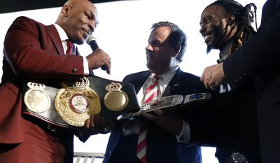New Jersey Gov. Chris Christie, center, is presented with a belt by boxer Mike Tyson, left, for Christie's work in promoting help for ex-prisoners re-entering society, during the 4th Annual New Jersey Prisoner Reentry Conference, Thursday, April 13, 2017, in Jersey City, N.J. (AP Photo/Julio Cortez)