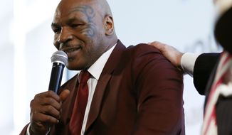 Boxer Mike Tyson is patted on the shoulder by New Jersey Gov. Chris Christie while speaking about his life post prison during the 4th Annual New Jersey Prisoner Reentry Conference, Thursday, April 13, 2017, in Jersey City, N.J. During the event, Tyson presented Christie with a championship belt for his efforts in helping former prisoners reinstall themselves into society. (AP Photo/Julio Cortez)
