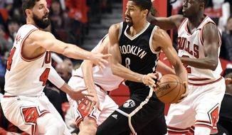 Brooklyn Nets guard Spencer Dinwiddie (8) is defended by Chicago Bulls forward Nikola Mirotic, left, and guard Jerian Grant, right, during the first half of an NBA basketball game in Chicago, Wednesday, April 12, 2017. (AP Photo/David Banks)