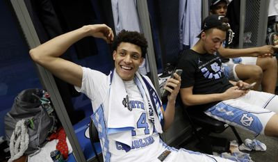 FILE - In this April 4, 2017, file photo, North Carolina forward Justin Jackson talks on his cell phone in the locker room after the championship game against Gonzaga at the Final Four NCAA college basketball tournament, in Glendale, Ariz. The school said Thursday, April 13, 2017, that Jackson will enter the NBA draft as a junior and hire an agent. (AP Photo/Mark Humphrey, File)