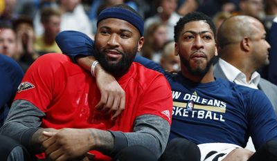 FILE - In this Friday, April 7, 2017, file photo, New Orleans Pelicans forwards DeMarcus Cousins, left, and Anthony Davis joke with each other as they sit on the bench and watch the second half of the team's NBA basketball game against the Denver Nuggets in Denver. The Pelicans did not make the playoffs for the second year in a row.  The All-Star break trade that paired Cousins and Davis showed considerable potential. (AP Photo/David Zalubowski, File)