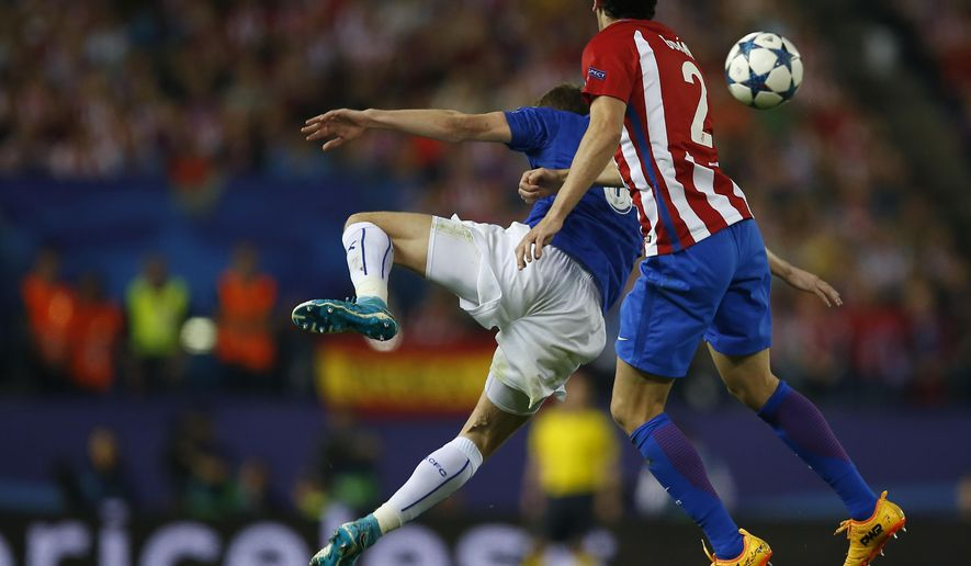 Leicester City's Jamie Vardy, left, vies for the ball with Atletico's Diego Godin during the Champions League quarterfinal first leg soccer match between Atletico Madrid and Leicester City at the Vicente Calderon stadium in Madrid, Spain, Wednesday, April 12, 2017. (AP Photo/Paul White)