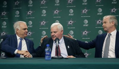 Dallas Stars newly hired NHL hockey team head coach Ken Hitchcock, center, is congratulated by team general manager Jim Nill, right, and president Jim Lites during a news conference in Dallas, Thursday, April 13, 2017. Hitchcock is returning to coach the Stars where he won the Stanley Cup in 1999. He has since coached the Philadelphia Flyers, Columbus Blue Jackets and St. Louis Blues. (AP Photo/LM Otero)
