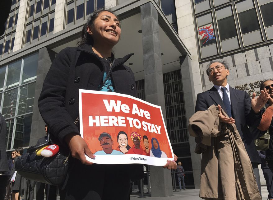Erica Leyva with the Services, Immigrant Rights and Education Network of San Jose, California, carries a message outside a courthouse in San Francisco where a federal judge heard arguments in a lawsuit challenging President Trump's executive order to withhold funding from communities that limit cooperation with immigration authorities. (Associated Press/File)