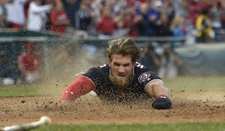 Washington Nationals' Bryce Harper slides home to score the winning run on a hit by Daniel Murphy during the tenth inning of a baseball game against the Philadelphia Phillies, Friday, April 14, 2017, in Washington. (AP Photo/Nick Wass)