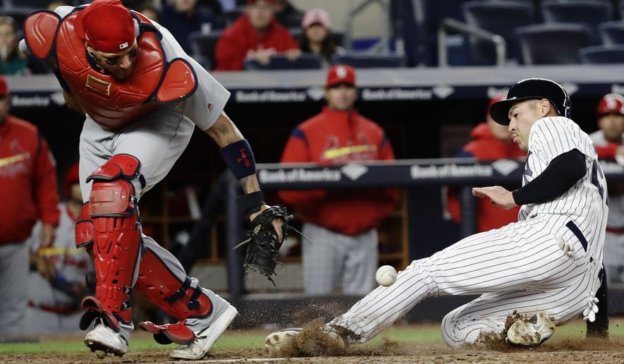 New York Yankees' Jacoby Ellsbury, right, scores on a throwing error by St. Louis Cardinals' Kolten Wong as catcher Yadier Molina fields the throw at home plate during the fifth inning of a baseball game Friday, April 14, 2017, in New York. (AP Photo/Frank Franklin II)