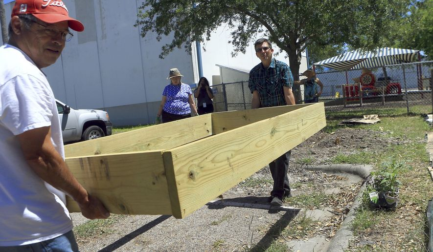 In this Monday, April 3, 2017 photo, Benny Prado, right, and County Extension Agent Kevin Gibbs from Texas A&M AgriLife prepare an area to plant vegetables and flowers at a community garden at the YWCA in Corpus Christi, Texas. (Gabe Hernandez /Corpus Christi Caller-Times via AP)
