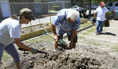 In this Monday, April 3, 2017 photo, Cristina Herrera, left, and David Haller, right, grab soil as they prepare to plant vegetables, herbs and flowers at the community garden at the YWCA in Corpus Christi, Texas. (Gabe Hernandez /Corpus Christi Caller-Times via AP)