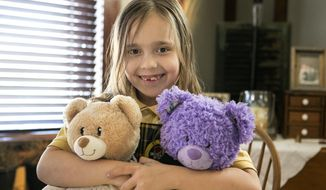 In this March 15, 2017 photo, Noa Grace Welborn holds her own Build A Bears at her  home in Belleville, Ill. At Noa's request, her father set up a GoFundMe page so she could make Build-A-Bears for other children. Noa and the doners from the GoFundMe effort, raised enough money to make 33 teddy bears for the Belleville Police Department to distribute them to scared children in troubling situations. (Derik Holtmann/Belleville News-Democrat, via AP)