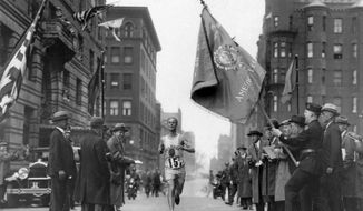 FILE - In this April 19, 1930 file photo, veteran marathoner Clarence DeMar, of the Melrose American Legion Post, crosses the finish line to win the Boston Marathon in the last of his record seven wins in Boston. A new film that captures much of the Boston Marathon's colorful history premieres Saturday, April 15, 2017, in conjunction with the 121st running of the race on Monday. (AP Photo, File)
