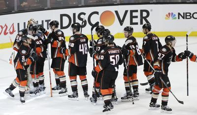 Anaheim Ducks players celebrate their team's 3-2 win against the Calgary Flames in Game 1 of a first-round NHL hockey Stanley Cup playoff series Thursday, April 13, 2017, in Anaheim, Calif. (AP Photo/Jae C. Hong)