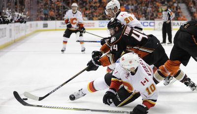 Anaheim Ducks' Nate Thompson, center, fights for the puck with Calgary Flames' Troy Brouwer, top, and Kris Versteeg during the first period in Game 1 of a first-round NHL hockey Stanley Cup playoff series Thursday, April 13, 2017, in Anaheim, Calif. (AP Photo/Jae C. Hong)