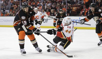 Anaheim Ducks' Ryan Getzlaf, left, shoots under the defense by Calgary Flames' Matt Bartkowski during the second period in Game 1 of a first-round NHL hockey Stanley Cup playoff series Thursday, April 13, 2017, in Anaheim, Calif. (AP Photo/Jae C. Hong)