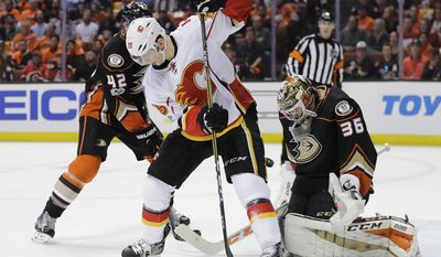 Anaheim Ducks goalie John Gibson, right, makes a save as Calgary Flames' Alex Chiasson stands in front of him during the first period in Game 1 of a first-round NHL hockey Stanley Cup playoff series Thursday, April 13, 2017, in Anaheim, Calif. (AP Photo/Jae C. Hong)