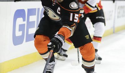 Anaheim Ducks' Ryan Getzlaf moves the puck as Calgary Flames' Matthew Tkachuk watches during the second period in Game 1 of a first-round NHL hockey Stanley Cup playoff series Thursday, April 13, 2017, in Anaheim, Calif. (AP Photo/Jae C. Hong)