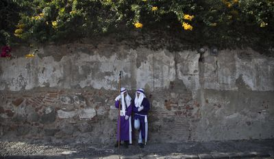 La Merced Catholic church penitents wait to participate in the Good Friday procession along the streets of Antigua, Guatemala, Friday, April 14, 2017. Around the world, Christians are coming together in observance of Good Friday, which they believe was the day Jesus was crucified. (AP Photo/Luis Soto)