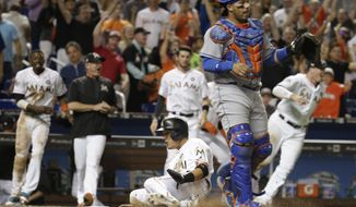 Miami Marlins' Miguel Rojas, center, scores the winning run past New York Mets catcher Rene Rivera, right, on a double hit by J.T. Realmuto during the ninth inning of a baseball game Friday, April 14, 2017, in Miami.  (AP Photo/Lynne Sladky)