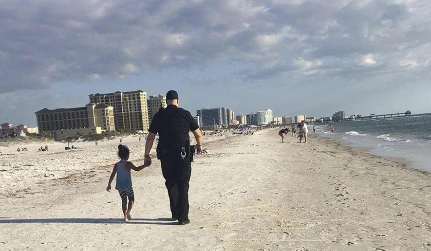 In this April 11, 2017, image provided by Amy Amerell, Clearwater police officer Rich Edmonds holds the hand of a 6-year-old girl on Clearwater Beach, Fla. The girl wandered away from her family and approached another family who called police for assistance. When the child refused to get in the officer's car, he walked her down the beach until they found her family. (Courtesy of Amy Amerell via AP)