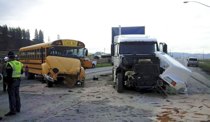 In this photo provided by the Washington State Patrol, emergency personnel work the scene of a crash involving a school bus and semi-truck Friday, April 14, 2017, near Colville, Wash. A student was taken to a hospital and several others suffered none life-threatening injuries in a crash involving a semi-truck and a school bus in eastern Washington state. Washington State Patrol Trooper Jeff Sevigney said that there were 25 elementary school students and a driver on the bus. (Washington State Patrol via AP)