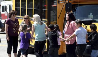 In this April 10, 2017, photo, North Park Elementary teaching assistant Jennifer Downing, right, evacuates the building with students after a shooting occurred at the school in San Bernardino, Calif. Downing said she thinks the shooter, Cedric Anderson, would have killed others if he hadn't run out of bullets and stopped to reload Monday.Anderson fatally shot himself after killing his estranged wife, teacher Karen Elaine Smith, and an 8-year-old boy, Jonathan Martinez, in a special-education classroom at North Park Elementary. (John Valenzuela/The Press-Enterprise via AP)