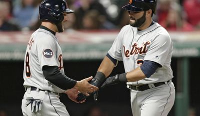 Detroit Tigers' Alex Avila, right, is congratulated by Tyler Collins after Avila hit a two-run home run, scoring Colins, off Cleveland Indians starting pitcher Trevor Bauer during the sixth inning of a baseball game, Friday, April 14, 2017, in Cleveland.. (AP Photo/Tony Dejak)