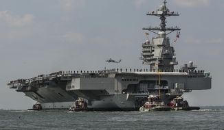 As crew members stand on the deck, the aircraft carrier USS Gerald R. Ford heads to the Norfolk, Va., naval station on Friday, April 14, 2017 after almost a week of builder's trials during which the ships systems were tested. Construction on the Ford started in 2009. The $12.9 billion carrier experienced more than a year's delay and cost overruns. (Bill Tiernan/The Virginian-Pilot via AP)