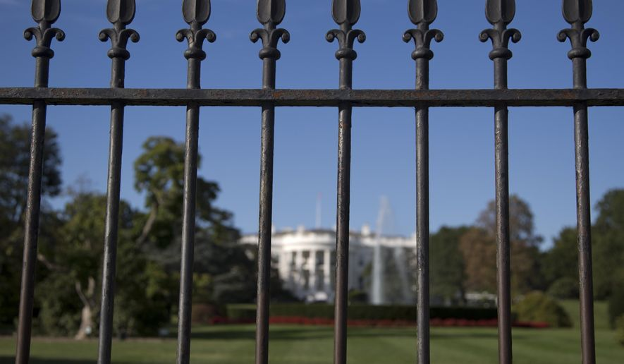 In this file photo taken Sept. 22, 2014, the iron perimeter fence lines the South Lawn of the White House in Washington. (AP Photo/Carolyn Kaster)
