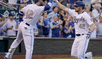Kansas City Royals' Brandon Moss, right, celebrates with Paulo Orlando after hitting a solo home run during the fourth inning of a baseball game against the Los Angeles Angels, Saturday, April 15, 2017, in Kansas City, Mo. (AP Photo/Charlie Riedel)