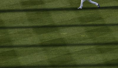 Kansas City Royals starting pitcher Nathan Karns warms up in the outfield before a baseball game against the Los Angeles Angels, Saturday, April 15, 2017, in Kansas City, Mo. (AP Photo/Charlie Riedel)