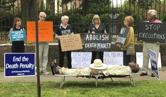This photo provided by Cheryl Simon shows Pulaski County Circuit Judge Wendell Griffen taking part of an anti-death penalty demonstration outside the Governor's Mansion Friday, April 14, 2017 in Little Rock, Ark.  Griffen issued a temporary restraining order Friday blocking the state from using its supply of vecuronium bromide after a company said it had sold the drug to the state for medical purposes, not capital punishment.   Local media outlets had tweeted photos and video of Griffen appearing to mimic an inmate strapped to a gurney at the demonstration.   Attorney General Leslie Rutledge's office said she planned to file an emergency request with the state Supreme Court to vacate Griffen's order, saying Griffen shouldn't handle the case.  (Cheryl Simon via AP)