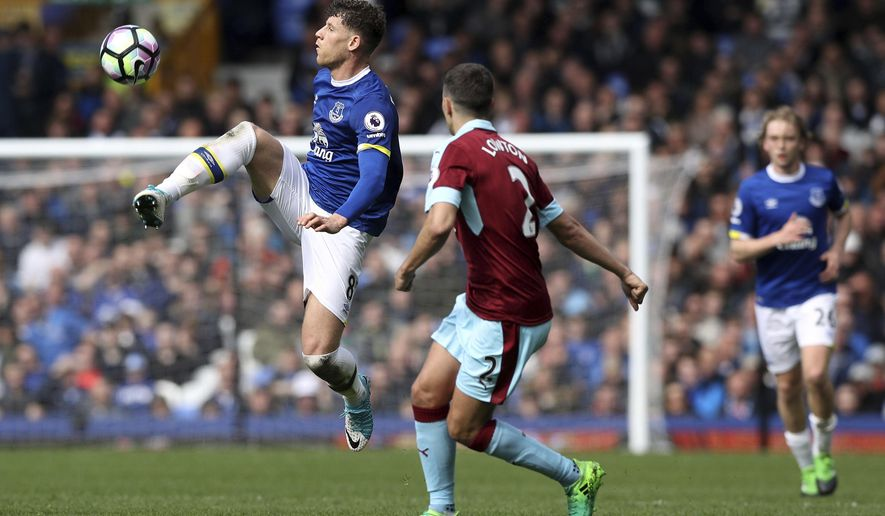 Everton's Ross Barkley, left, and Burnley's Matthew Lowton battle for the ball during their English Premier League soccer match at Goodison Park, Liverpool, England, Saturday, April 15, 2017. (Martin Rickett/PA via AP)