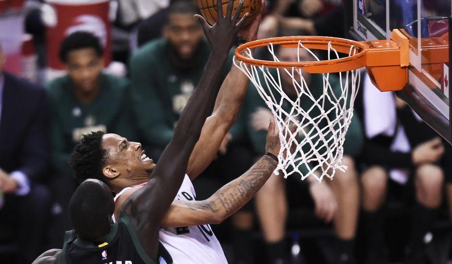 Toronto Raptors guard DeMar DeRozan (10) is blocked by Milwaukee Bucks forward Thon Maker (7) during second-half NBA playoff basketball game action in Toronto, Saturday, April 15, 2017. (Nathan Denette/The Canadian Press via AP)