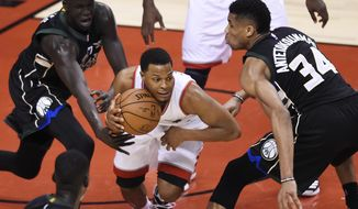 Toronto Raptors guard Kyle Lowry (7) protects the ball from Milwaukee Bucks forwards Giannis Antetokounmpo (34) and Thon Maker (7) during second-half NBA playoff basketball game action in Toronto, Saturday, April 15, 2017. (Nathan Denette/The Canadian Press via AP)