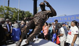 A bronze statue of Brooklyn Dodgers great Jackie Robinson is unveiled outside Dodger Stadium before the Los Angeles Dodgers' baseball game with the Arizona Diamondbacks, Saturday, April 15, 2017, in Los Angeles. (AP Photo/Jae C. Hong)