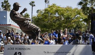 A bronze statue of Brooklyn Dodgers' legend Jackie Robinson is unveiled outside Dodger Stadium before the team's baseball game with the Arizona Diamondbacks, Saturday, April 15, 2017, in Los Angeles. (AP Photo/Jae C. Hong)