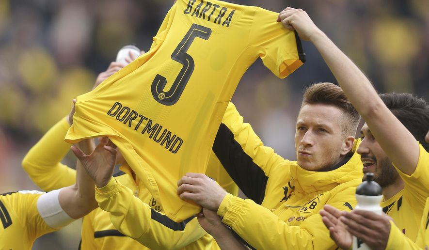 Dortmund's Marco Reus, Nuri Sahin, right,  and other players hold up the jersey of teammate Marc Bartra after  the German Bundesliga soccer match between Borussia Dortmund and Eintracht Frankfurt in Dortmund, Germany,Saturday, April 15, 2017. Marc Bartra was heavily injured after the bomb attack on Dortmund's team bus on the April 11, 2017. (Ina Fassbender/dpa via AP)