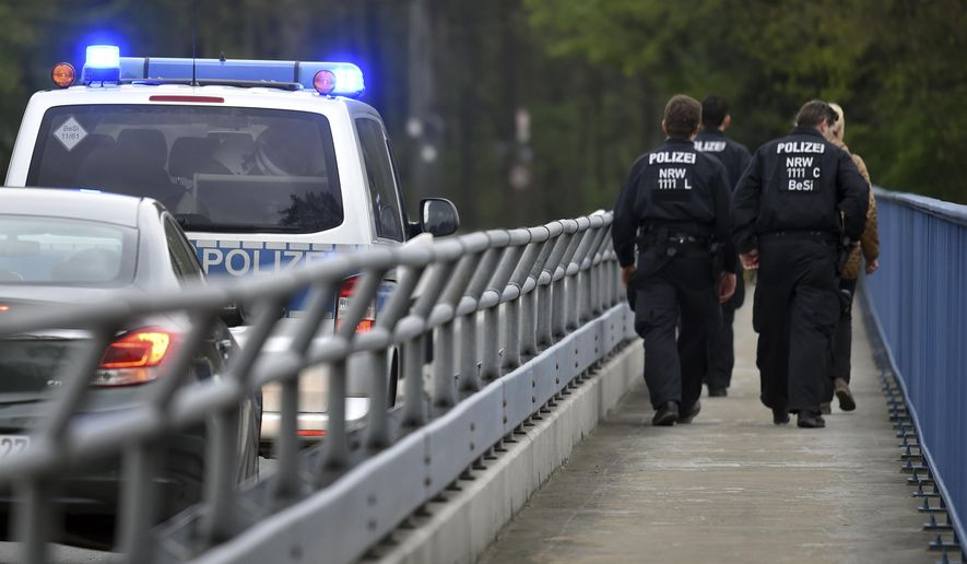 Policemen are on their way to search for evidence in Dortmund, Germany, Friday, April 14, 2017. After the attack on the team bus of Borussia Dortmund soccer club Tuesday, April 11, 2017,  the used explosives and the ignition mechanism are in focus of the investigations (Caroline Seidel/dpa via AP)